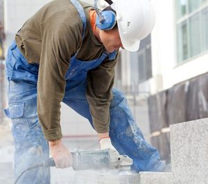 Silica Exposure Violation - Man cutting concrete without respirator