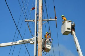 Workers in buckets working on power lines in the sun - sun protection - worksite medical