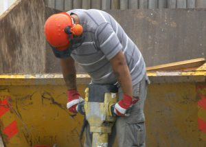 Worker Jackhammering on a loud job site - Hearing Conservation Program - Worksite Medical