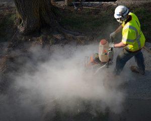 Worker breaking concrete, releasing silica dust