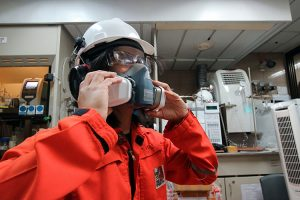 Respiratory Health Hazards - Woman Wearing a Respirator at Work - Personal Protective Equipment